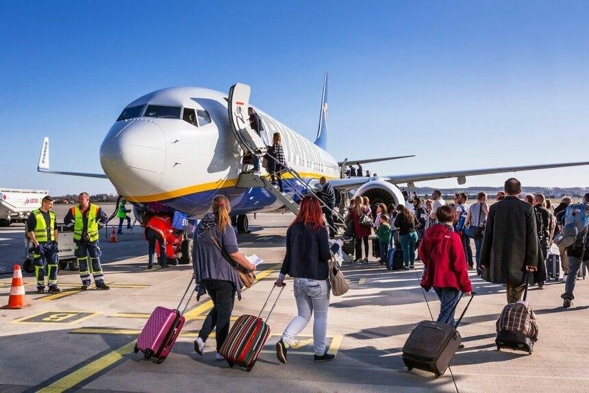 Пассажиры с чемоданами идут по взлетной полосе на посадку в самолет.